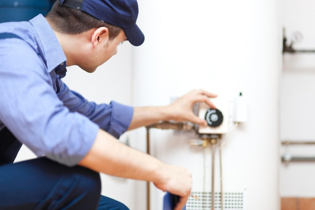 Technician adjusting water heater settings.