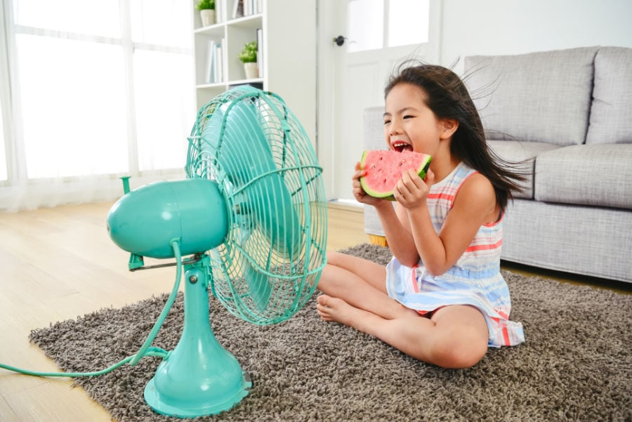 Small girl eating watermelon on the floor in front of a fan.