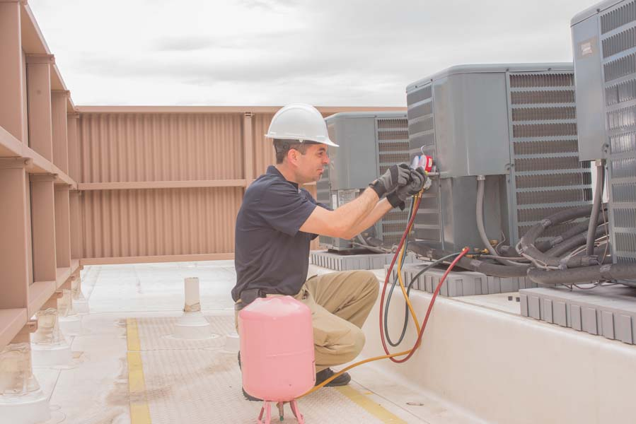 Technician taking a cover plate off an air conditioner condenser.