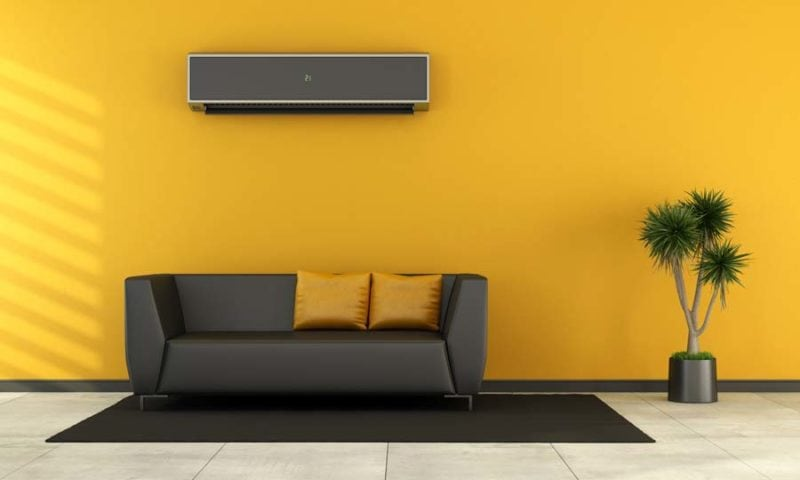 Modern living room with black couch and ductless air conditioner (AC) on wall - rendering