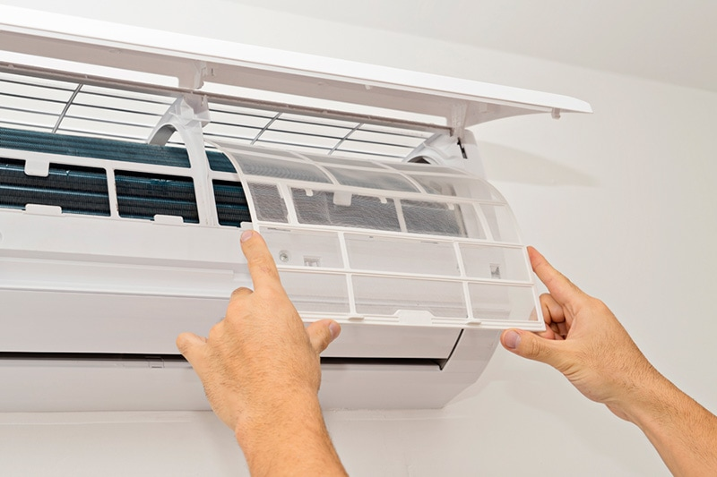 Hands opening the panel of a ductless system | What Maintenance Is Needed For A Ductless System? | Wheaton, IL