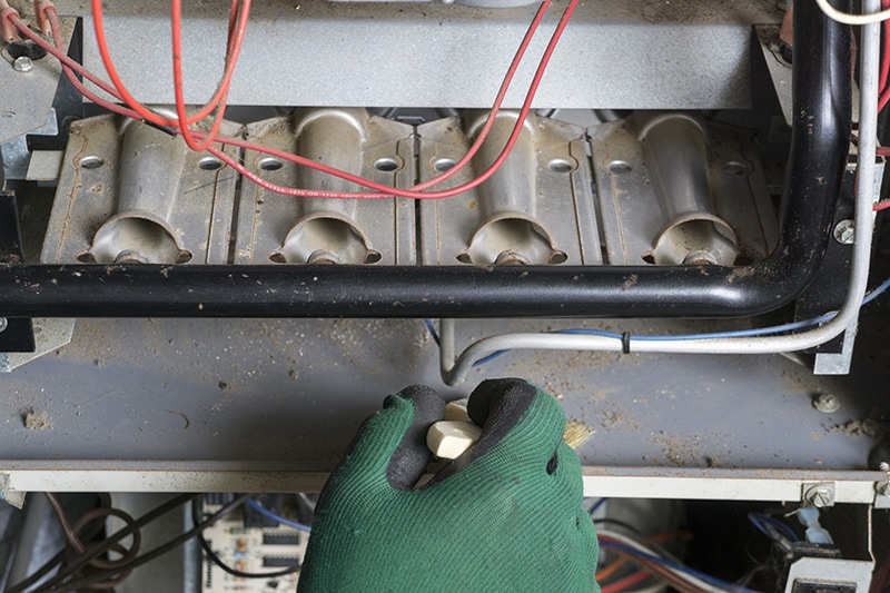 A gloved hand repairing the inside of an appliance | 5 Reasons to Schedule a Fall Furnace Clean and Check | Wheaton, IL