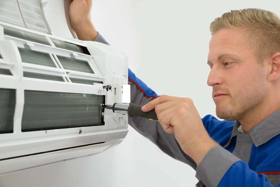 Portrait Of Young Male Technician Repairing Air Conditioner in West Chicago, IL