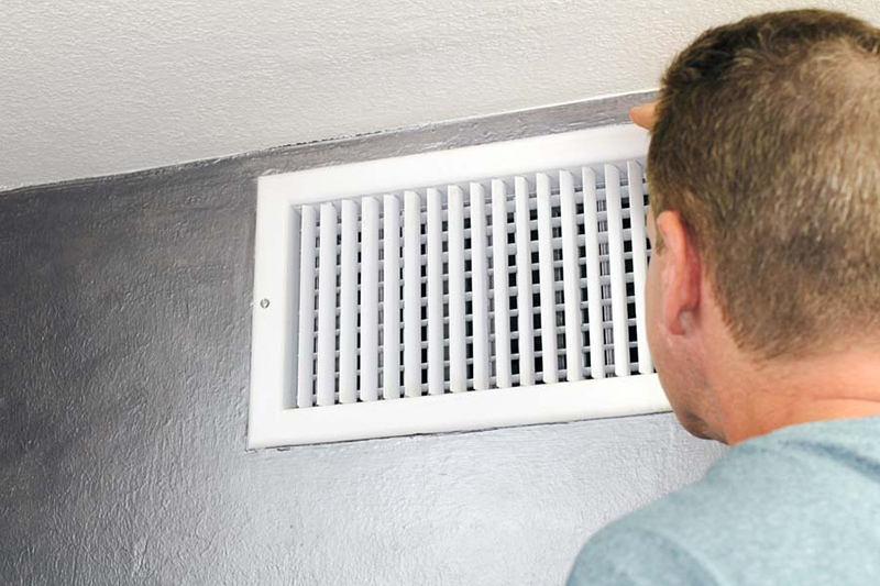 man looking at white air vent on the wall
